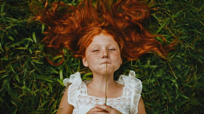 Little girl wearing white lacy summer dress lying on green grass with long red hair spread out.