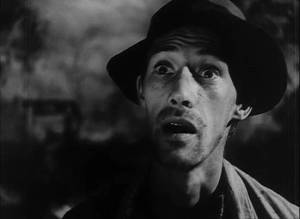 B & W movie still--headshot of unshaven thin man wearing black hat with earnest expression.
