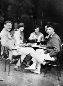 1920s B & W Photo of several men and women sitting at a cafe table wearing casual clothing from the period.