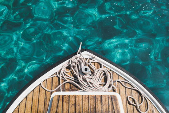 Picture of bow of wooden rowboat in sparkling green water.