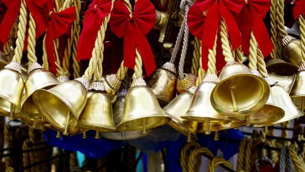 Photo shows more than a dozen small brass bells on gold cords with red bows above them.