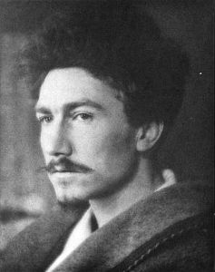 B & W Photo. Profile of Ezra Pound, young man with dark curly hair and thin dark mustache. Important in promoting tenets of American Modernist Literature.