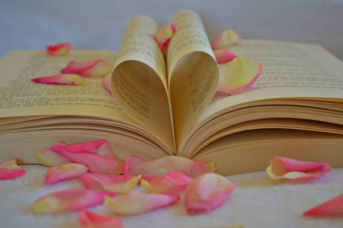 Open book with top pages tucked into heart shape, with scattered pink petals.