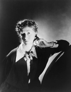 Dramatically lit B & W Photo of Marianne Moore, closely-curled hair with black dress and long pointed white collar. Important to American Modernist Literature.