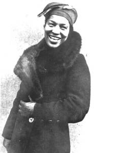 B & W Photo of Zora Hurston, African American woman smiling, wearing 1930s style coat with large fur collar and stylish turban-type hat. Important to American Modernist Literature.