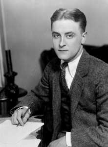 Photo of young writer F. Scott Fitzgerald, sitting at desk with paper and pen, looking up. 1921.