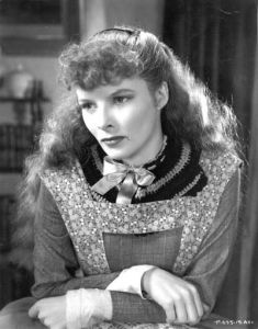 Photo of Katherine Hepburn dressed as Jo March, wavy long hair bow at neck, wearing printed pinafore over plain gray dress, looking serious.