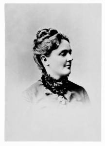 Old-fashioned photo of young woman-headshot in profile. Light brown hair coiled on top of head, dress buttoned up to neck.