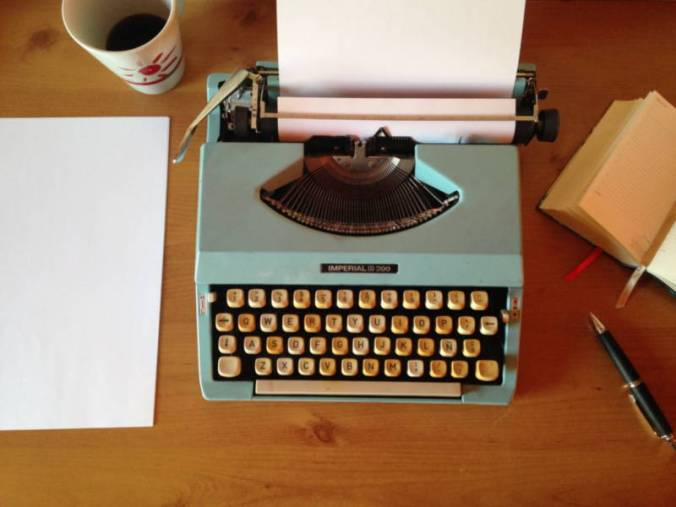 20th century typewriter in turquoise, shown with paper inserted and cup of coffee to the left--writer's characterization tools!