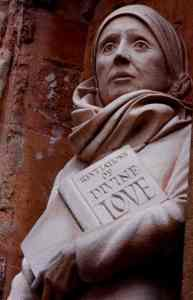 Statue showing head and torso of Julian of Norwich. She is holding her famous work, Revelations of Divine Love.