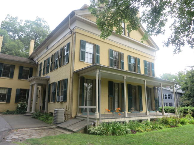 The Homestead, a large two-story yellow house with green shutters in federal style, was home to Emily Dickinson.