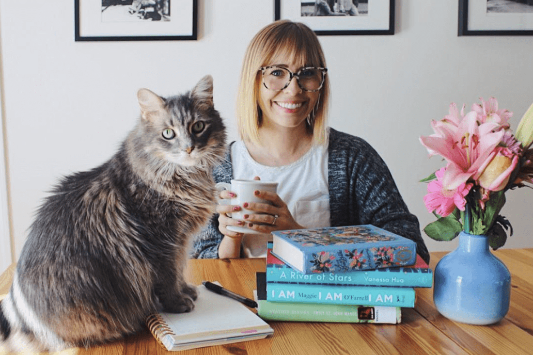 woman sits holding mug with a stack of books on the table and a grey cat by the books