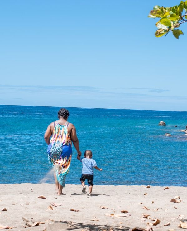 black woman walks on beach with her son