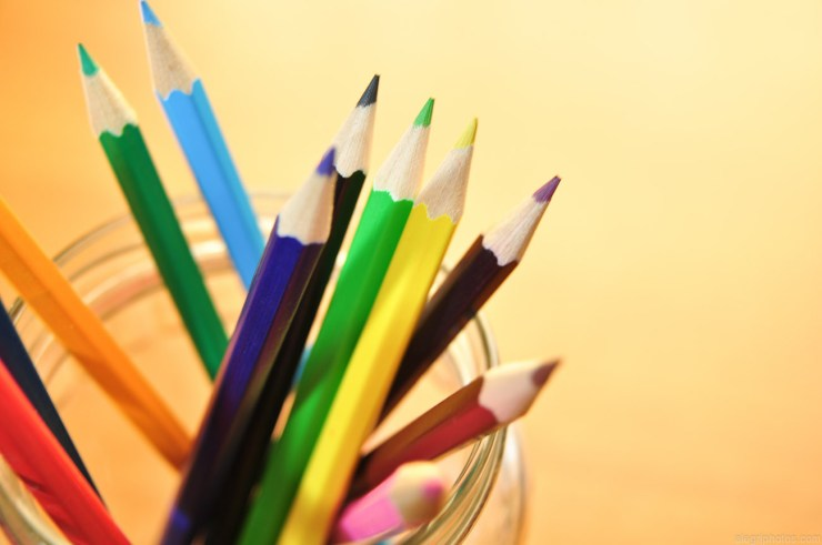 A jar of colored pencils with a yellow gradient background. The colored pencils are green, blue, purple, yellow, black, orange, red, and pink.
