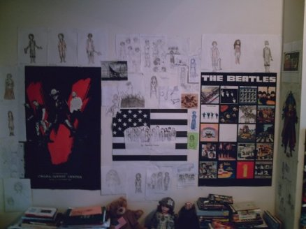 College bedroom wall with posters and character drawings