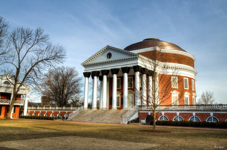 University of Virginia building--it has a dome top and ornate white and black columns at its entrance. There are steps going up to the building and a field in front of it.
