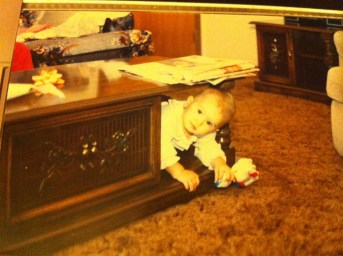 J.R. Dawnson as a young child hiding under a wooden table