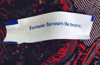 """Fortune Favors the Brave"" on a fortune cookie paper."