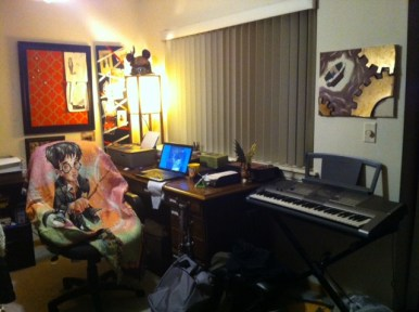 My current writing room, 2014--a chair with a Harry Potter throw blanket on it, a laptop on a desk, and a keyboard are in the room.