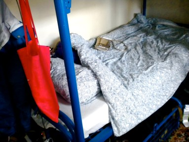 A lower bunk in a European hostel with a blue frame, a gold purse on the blue and white floral comforter, and a red tote bag hanging
