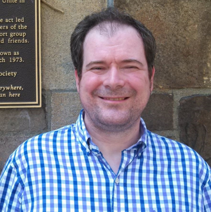 A picture of Whitter Strong in a blue gingham shirt in front of a stone building with a plaque to the left.