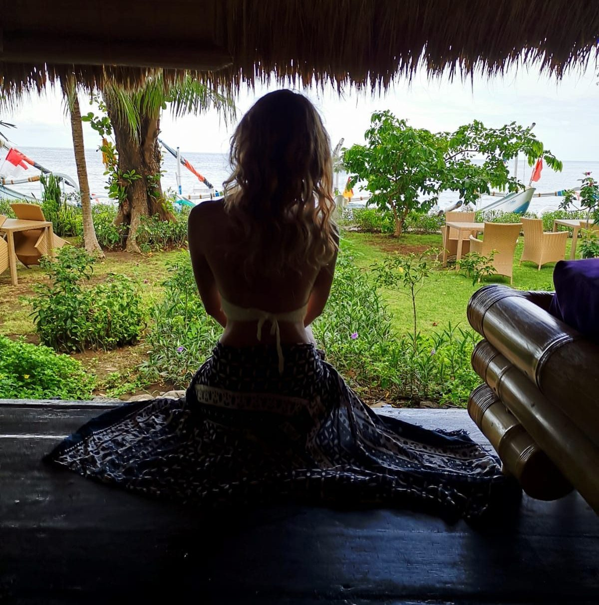 Good karma bungalow amed Bali, girl sitting on the floor.
