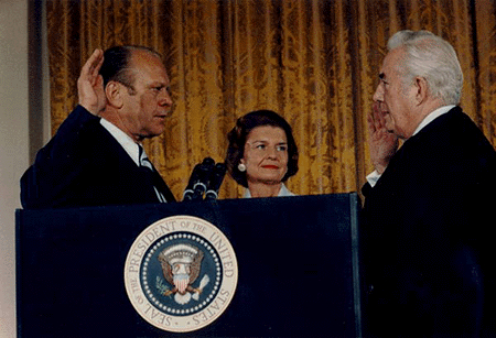 Gerald Ford on the left raises his right hand to take the oath of office for the President of the United States from Chief Justice Warren Burger on the right. Behind them is First Lady Betty Ford watching Chief Justice Burger.