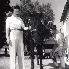 "1950s Ronald Reagan and Nancy Reagan putting Bridle on ""Tar Baby"" for a ride at Malibu Canyon Ranch ""Yearling Row"""