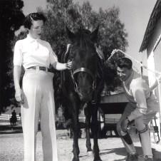 "1950s Ronald Reagan and Nancy Reagan putting Bridle on ""Tar Baby"" for a ride at Malibu Canyon Ranch ""Yearling Row"""