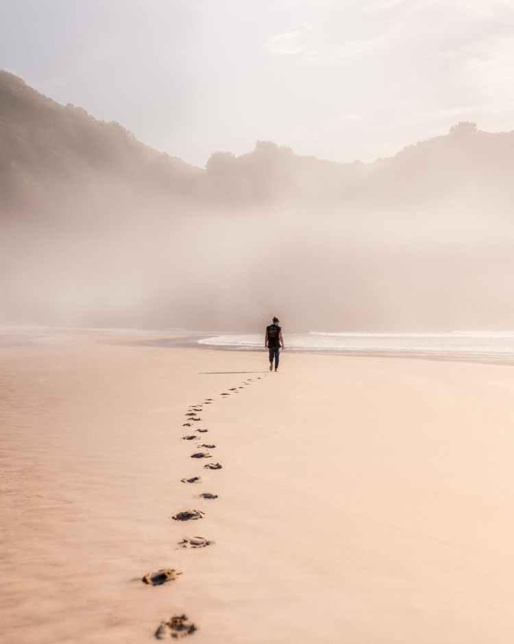 anonymous man walking on sandy seashore in misty weather