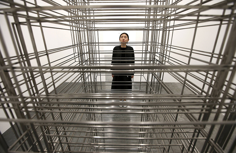 "A member of the gallery poses for a photograph next to a piece called ""Fit"", by artist Antony Gormley, which forms part of an exhibition entitled ""Fit"", at the White Cube gallery in London, Britain September 29, 2016.   REUTERS/Peter Nicholls"