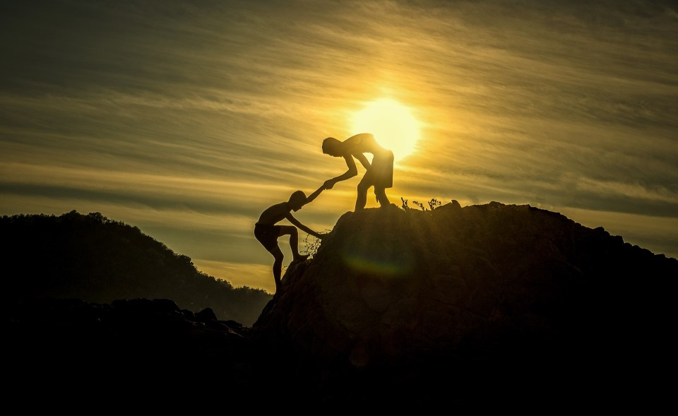one person helping another get to the top of the hill