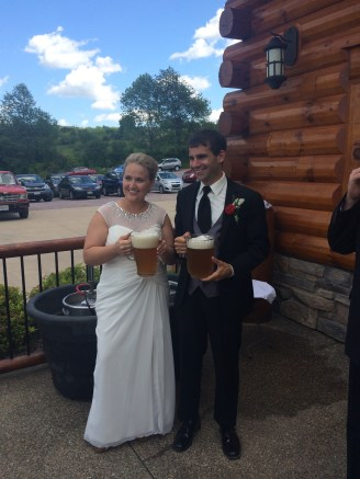 The newly married couple with pitchers of Spotted Cow beer.