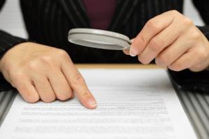 契約書と虫メガネ