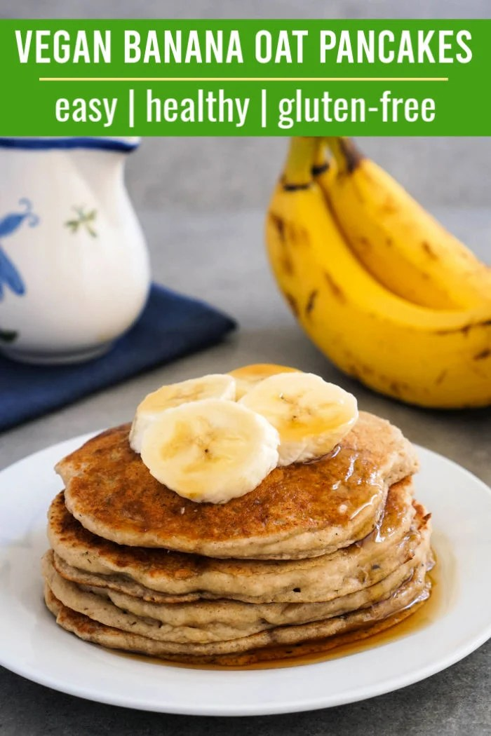 Vegan banana oat pancakes topped with bananas and maple syrup