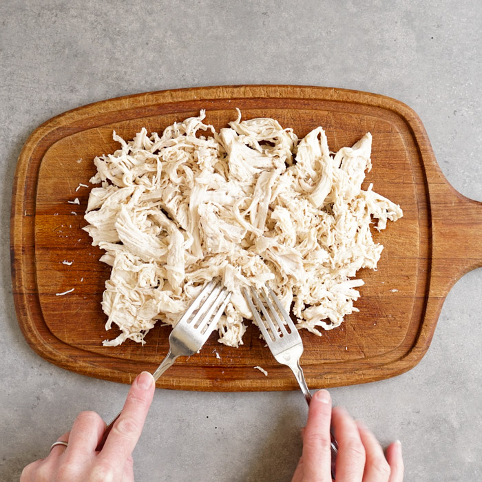 Shredding chicken on a cutting board