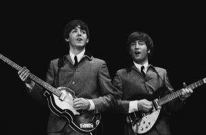"""This February 11, 1964 photo provided by Christie's auction house, from a collection of photos of The Beatles shot by photographer Mike Mitchell at the Washington Coliseum in Washington, D.C., shows Paul McCartney, left, and John Lennon during group's first US concert, two days after their Ed Sullivan appearance. The concert photos, taken when the photographer was just 18 years old, will be auctioned by Christie's in their sale """"The Beatles Illuminated: The Discovered Works of Mike Mitchell,"""" in New York on July 20, 2011. (AP Photo/Christie's, Mike Mitchell)"""
