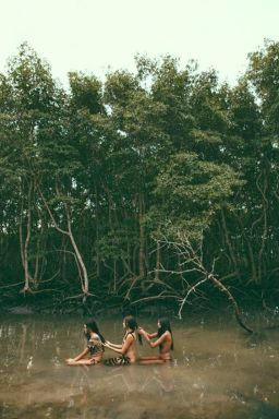 Three women sitting in a swamp braiding each others' hair