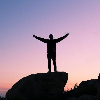 Man standing on rock at sunrise