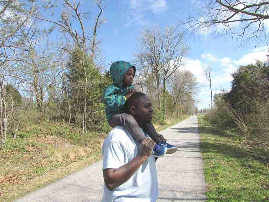 father and son on walking trail to save money and stay active