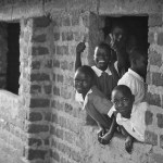 students lean out of classroom building window