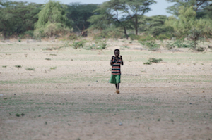 young child walking on a dirt path