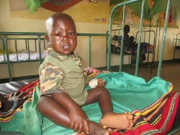 young child sits in hospital