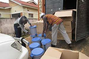Two men unload supplies from a storage container onto the ground