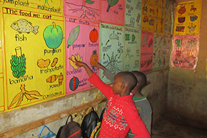 Two children in a classroom point to a chart of fruits and vegetables with names written in English
