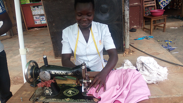 Scovia Achola sews a pink garment at her sewing table