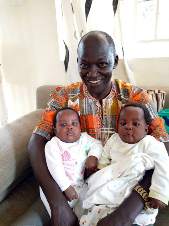 Francis, Caroline Tukugize's husband, sits with his infant twins in his lap. He is smiling.