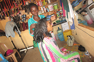 woman standing and combing the hair of another woman who is sitting in a beauty shop