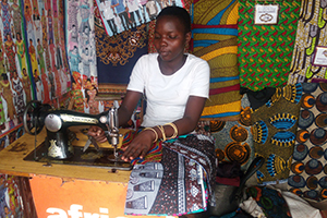 Woman sitting at sewing table sewing a garment
