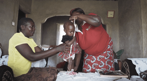 Our lead Community Health Worker, Euniter, measures a child's MUAC in her home.